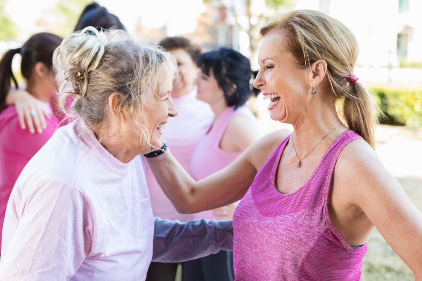 Pretty senior female friends laugh and enjoy one anothers' company after finishing breast cancer charity 5k race. One woman has her hand on the othe woman's shoulder as they laugh. People are talking in the background. The women are wearing pink work out clothing.